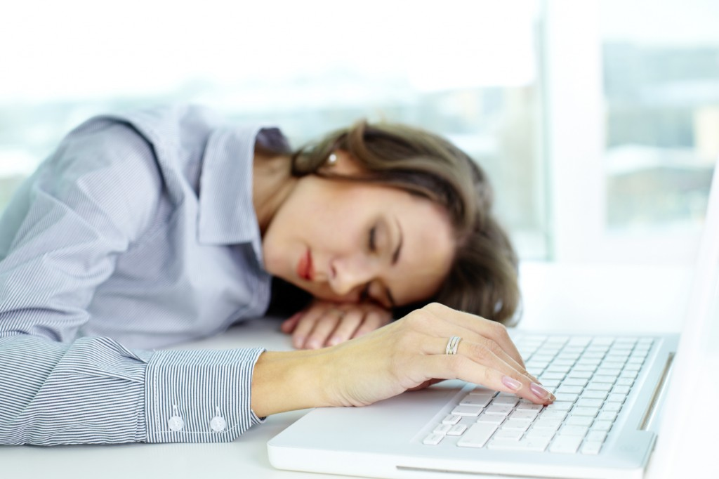 Young woman sleeping at workplace, her fingers touching keyboard